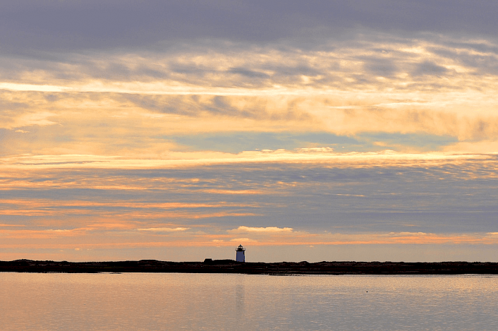 The sun sets over a lighthouse on Cape Cod